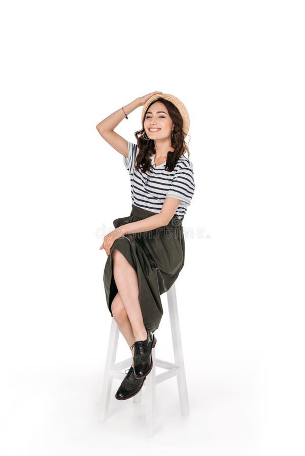 Młoda elegancka azjatykcia kobieta pozuje podczas gdy siedzący na krześle obrazy royalty free