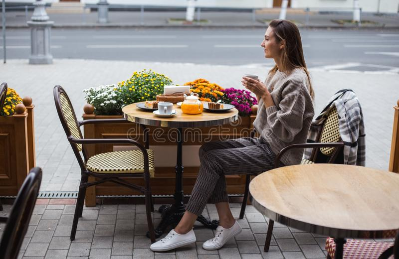 Młoda elegancka kobieta ma francuskiego śniadanie z kawy i torta obsiadaniem przy cukiernianym tarasem obrazy stock
