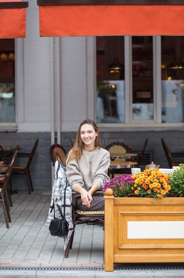 Młoda elegancka kobieta ma francuskiego śniadanie z kawy i torta obsiadaniem przy cukiernianym tarasem zdjęcie stock