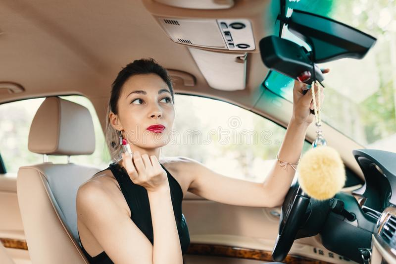 Młoda elegancka kobieta patrzeje w samochodowym widoku lustrze podczas gdy applyin fotografia stock