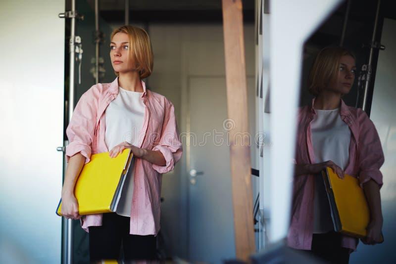 Młoda elegancka kobieta trzyma jaskrawą żółtą książkę stoi blisko półki w domowym wnętrzu zdjęcia royalty free