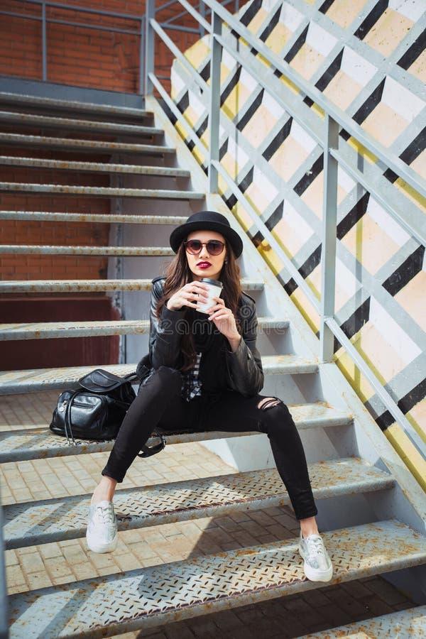 Młoda elegancka kobieta w miasta obsiadaniu i kawie ulicznej pić herbacie lub zdjęcie royalty free