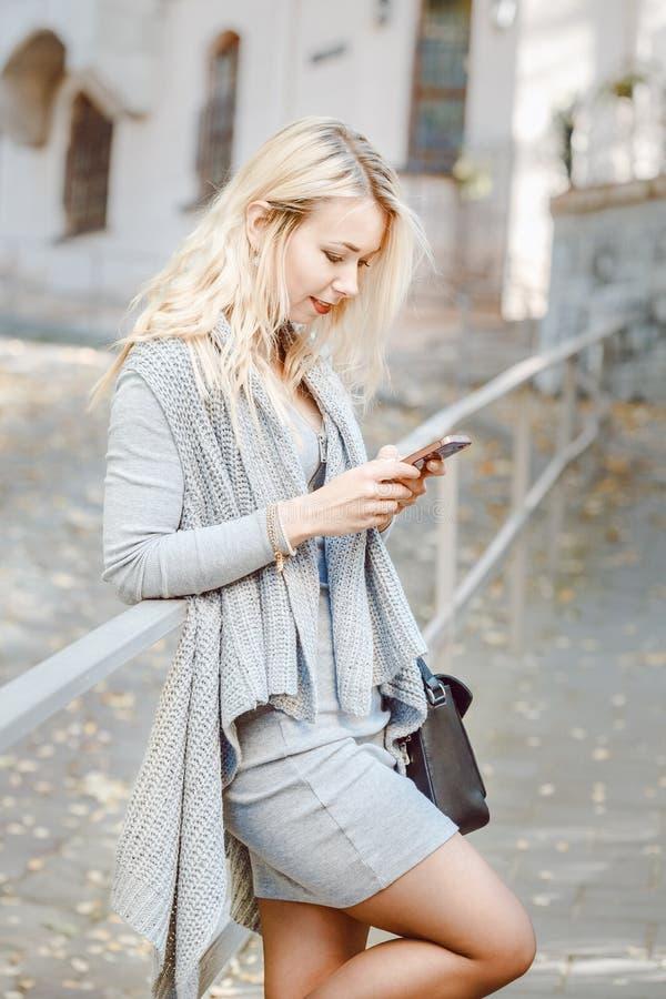 Młoda elegancka kobieta z mądrze telefonem ulica obrazy stock