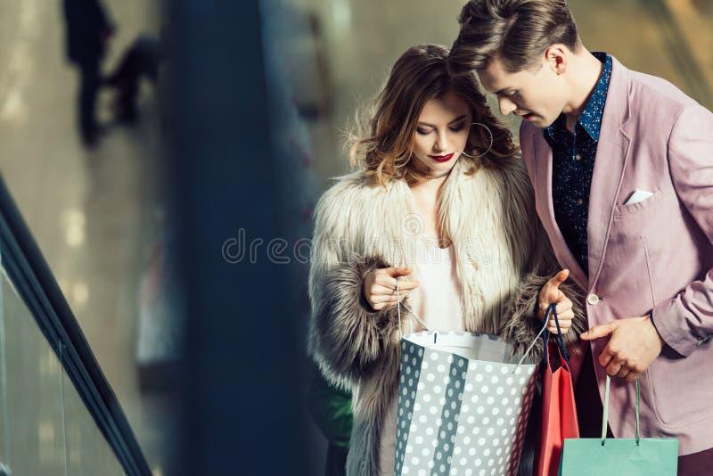 młoda elegancka para patrzeje w torba na zakupy zdjęcie royalty free