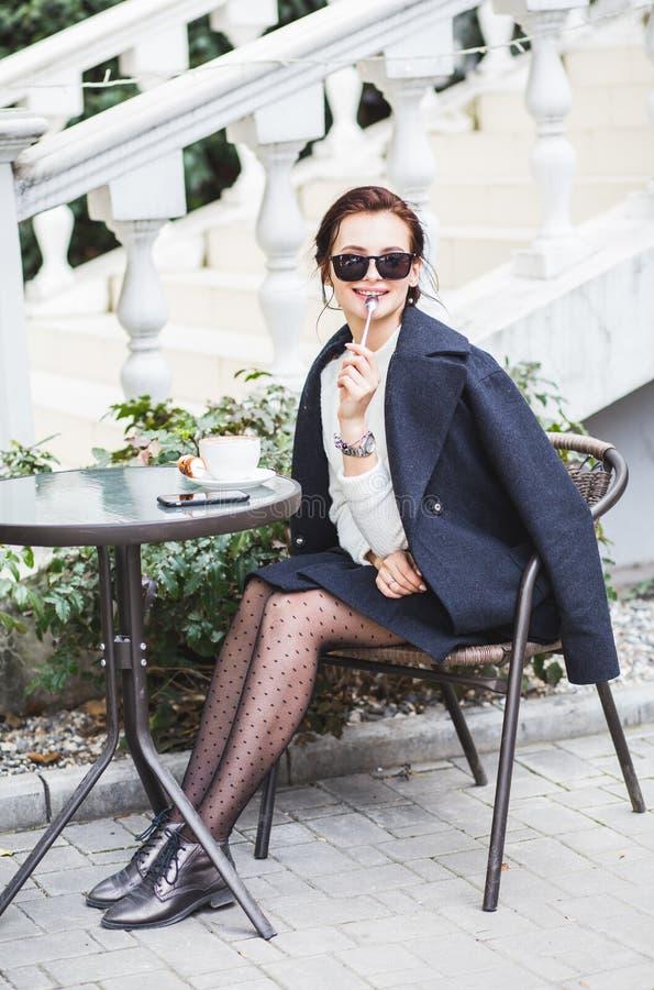 Młoda elegancka piękna kobieta siedzi w cukiernianej plenerowej pije kawie w okularach przeciwsłonecznych obrazy royalty free