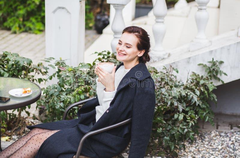 Młoda elegancka piękna kobieta siedzi w cukiernianej plenerowej pije kawie w okularach przeciwsłonecznych zdjęcie stock