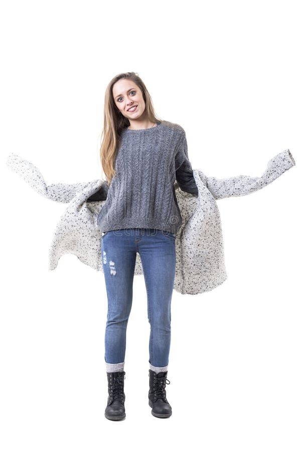 Młoda elegancka przypadkowa dziewczyna dostaje ubierającego stawiającego dalej trykotowego szarego kardigan nad bluzą obraz stock