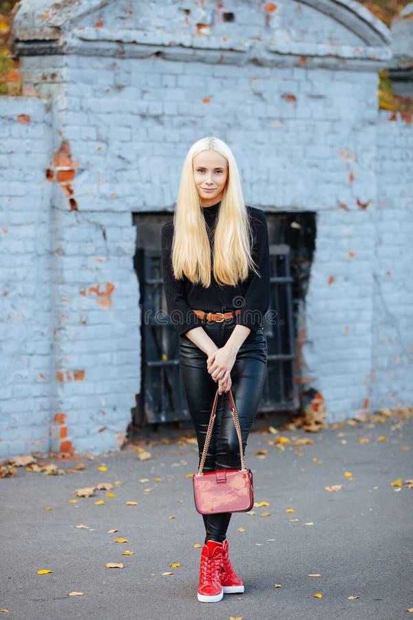 Młoda elegancka sporty blond piękna nastoletnia dziewczyna w czarny pozować przy parkiem na ciepłym spadku dniu przeciw staremu k zdjęcia stock