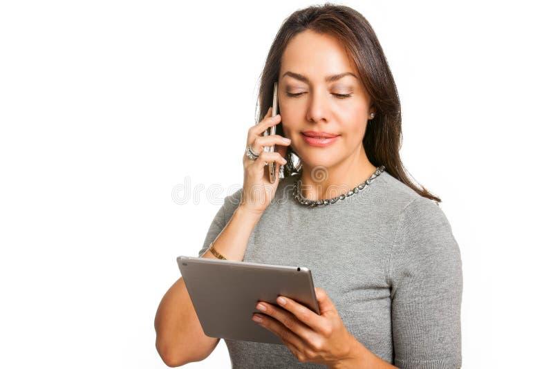 Młoda fachowa kobieta używa pastylkę i opowiadający na jej telefonie komórkowym odizolowywającym obrazy royalty free