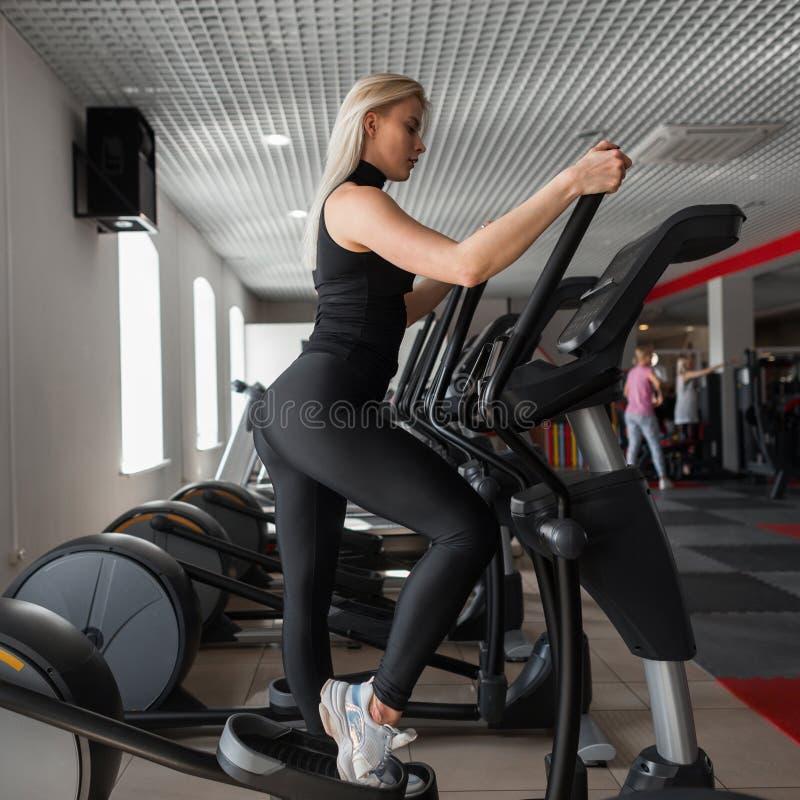 Młoda fachowa trener kobieta w czarnym sportswear w gym butach angażuje na stepper symulancie w sprawności fizycznej studiu obrazy stock
