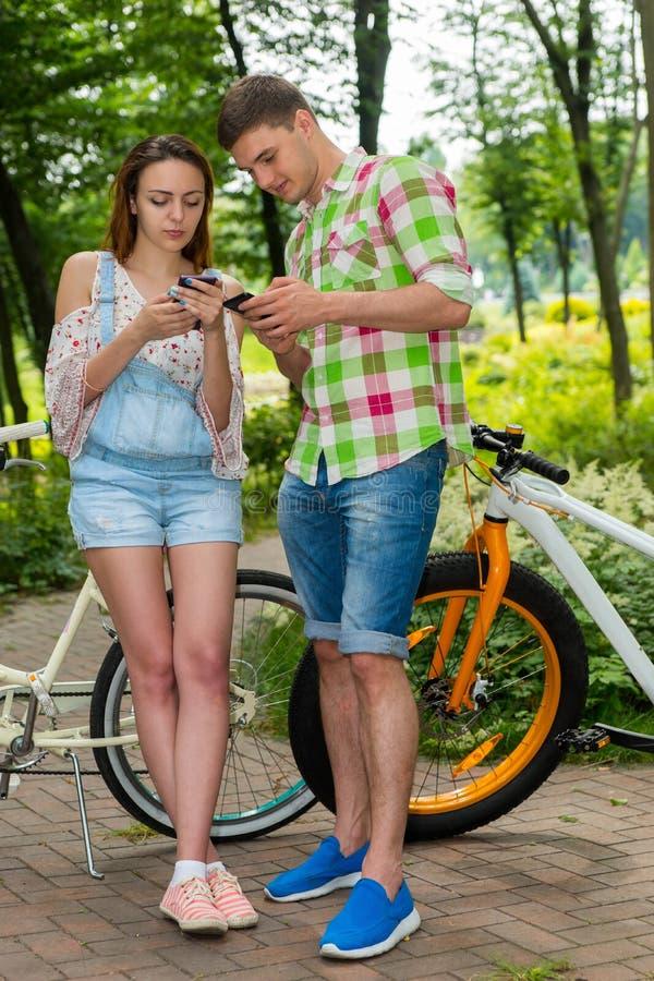 Młoda fasionable para surfuje internet z ich smartpho obraz stock