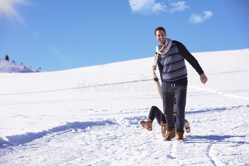 Młoda figlarnie para ma zabawy sanny puszka śnieg zakrywał wzgórze zdjęcie royalty free