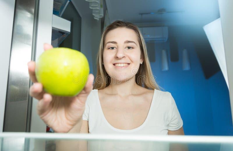 Młoda głodna kobieta bierze świeżego zielonego jabłka od refrigarot półki przy nocą obraz stock