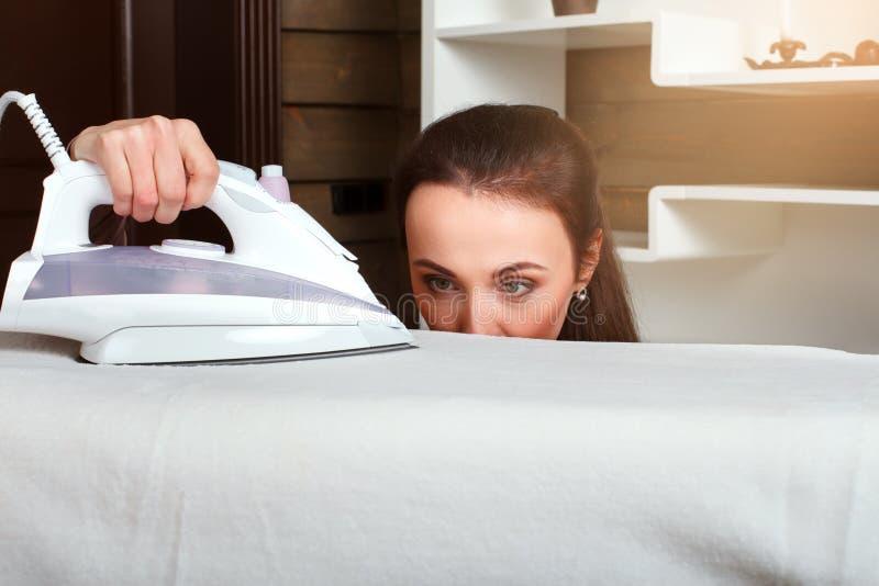 Młoda gospodyni domowej praca z parowym żelazem zdjęcia stock