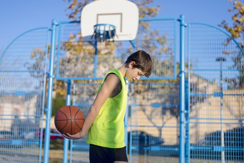 Młoda gracz koszykówki pozycja na sądzie jest ubranym kolor żółtego s fotografia royalty free