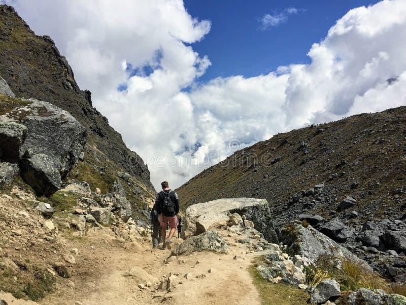 Młoda grupa międzynarodowi wycieczkowicze, prowadząca ich lokalnym inka przewdonikiem, żegluje Andes góry obrazy stock