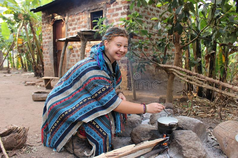 M?oda hipis kobieta w b??kitnym poncho kucharstwie na ogniska obozowisku w wiosce zdjęcia stock