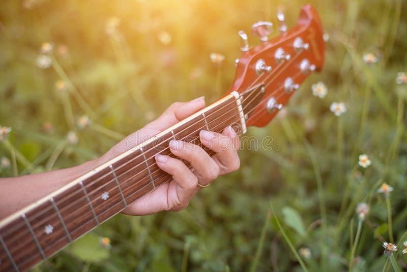Młoda hipsterka grająca na gitarze, by odpocząć na wakacjach, cieszyć się naturalnym i świeżym powietrzem zdjęcie royalty free