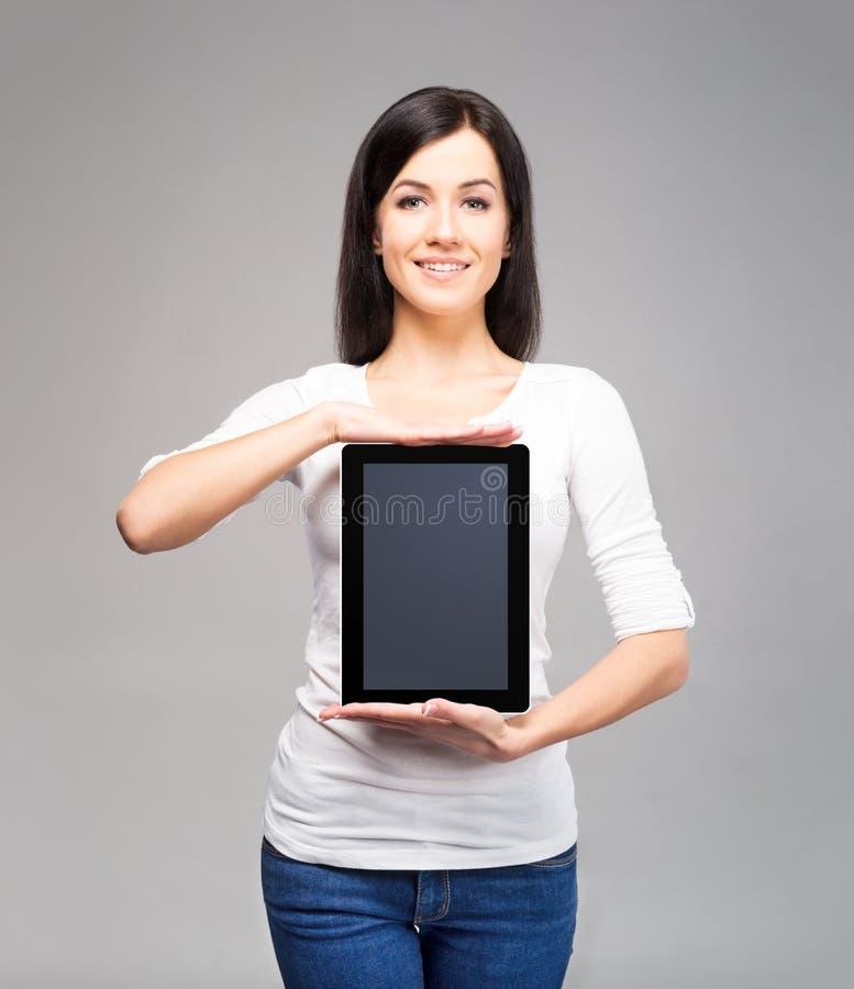 Młoda i atrakcyjna biznesowa kobieta trzyma pastylkę obrazy stock