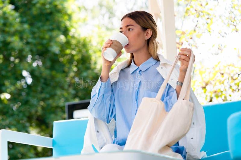 Młoda i atrakcyjna kobieta pije kawę od kawowego eco biodegradable filiżanki przy nowożytnym parkiem fotografia royalty free
