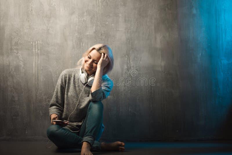 Młoda i atrakcyjna kobieta z hełmofonami, siedzi na podłoga Muzyka w wiszącej ozdobie app zdjęcia stock