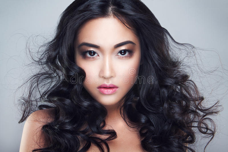 Młoda i piękna azjatykcia kobieta z kędzierzawym włosy fotografia stock