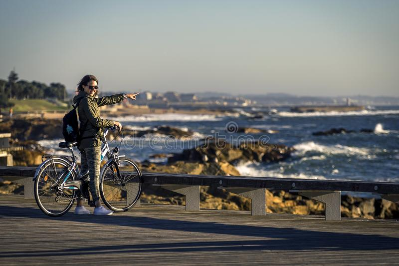 Młoda i piękna dziewczyna jedzie rower molem obok Atlantyckiego oceanu zdjęcia royalty free
