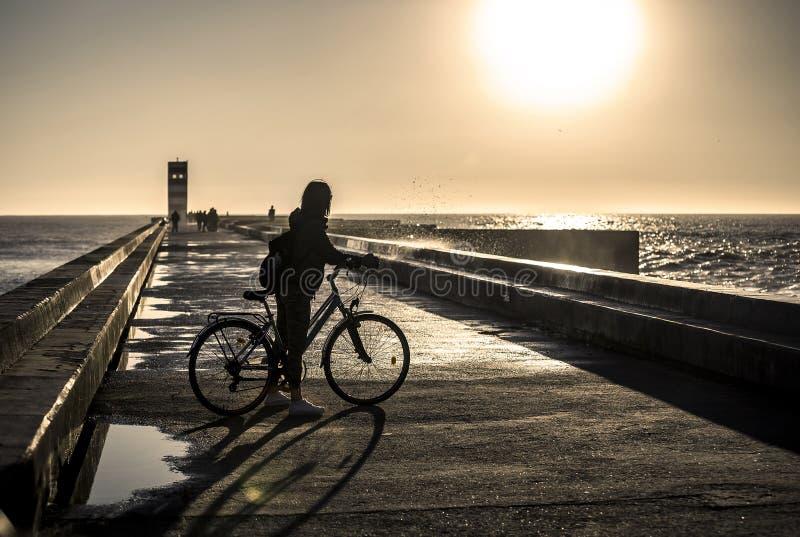 Młoda i piękna dziewczyna jedzie rower molem obok Atlantyckiego oceanu obrazy stock