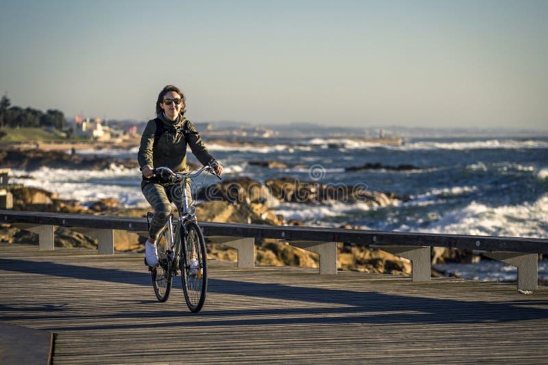 Młoda i piękna dziewczyna jedzie rower molem obok Atlantyckiego oceanu fotografia stock