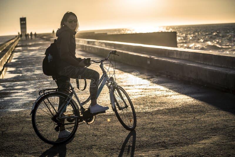 Młoda i piękna dziewczyna jedzie rower molem obok Atlantyckiego oceanu zdjęcie royalty free