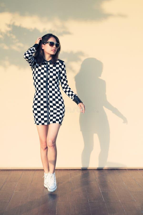 Młoda i piękna modniś kobieta przeciw światłu i cień na wa zdjęcia stock