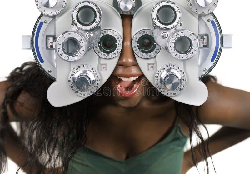 Młoda i szczęśliwa czarna afro Amerykańska kobieta sprawdza oczy ma celowniczego egzamin przy szpitalny patrzeć przez optometric  zdjęcia stock