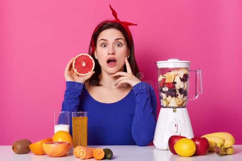 Młoda i zdrowa kobieta zaskakującego wyraz twarzy, chwytów grapefruitowy w jej ręce kawałek, odizolowywający nad różowym tłem obraz royalty free