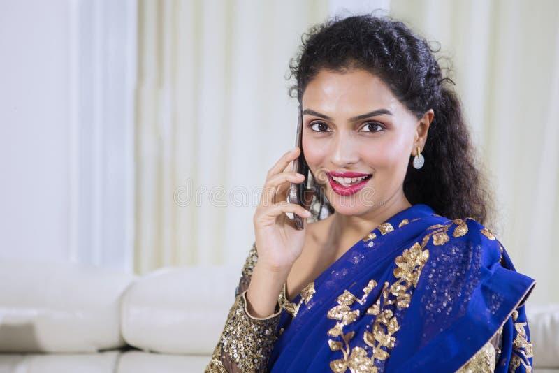 Młoda Indiańska kobieta mówi na telefonie w domu zdjęcie royalty free