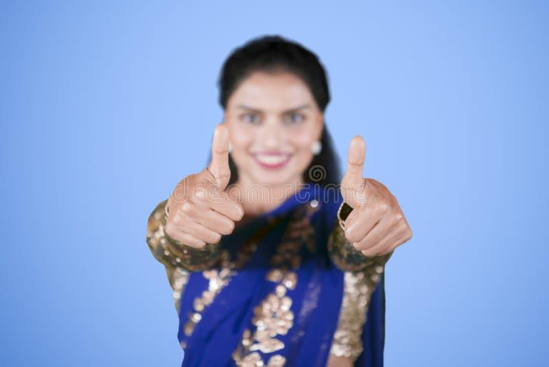 Młoda Indiańska kobieta pokazuje aprobaty na studiu obraz royalty free