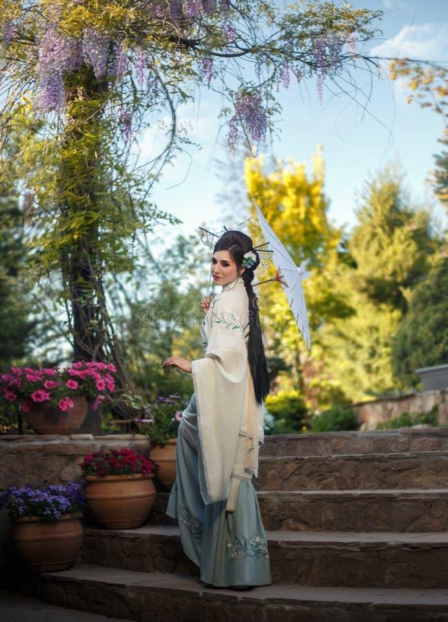 Młoda Japońska kobieta z długim, czarni włosy chodzi w bajecznie, kwitnienie ogród Na nim jest luksusowa zieleń obraz royalty free