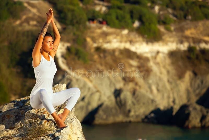 Młoda joga kobieta medytuje przy zmierzchem lub wschodem słońca w czarnym dennym Crimea fotografia royalty free