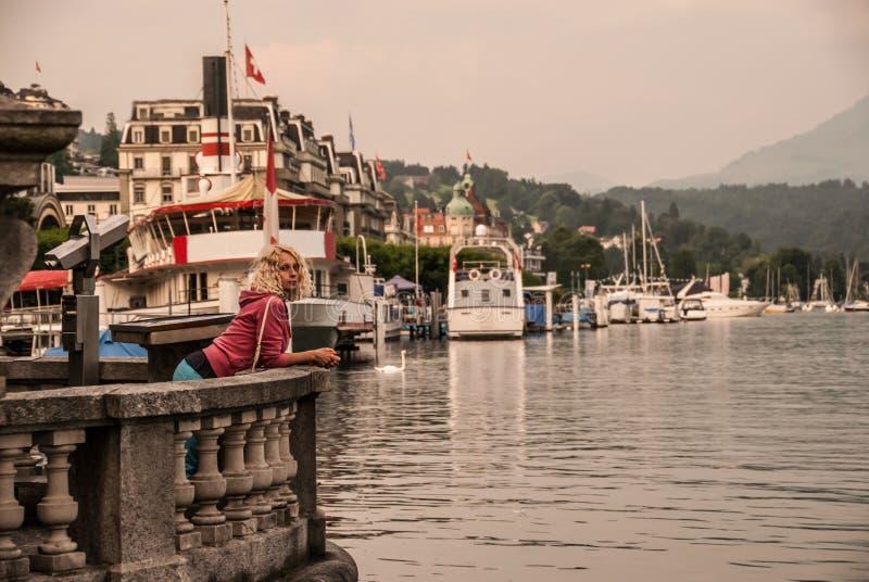 Młoda kędzierzawa blondynki kobieta dostaje niektóre odpoczynek na bulwarze w centrum lucerna, Szwajcaria fotografia royalty free