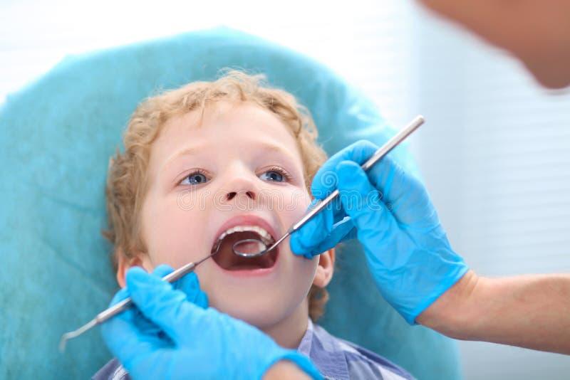 Młoda kędzierzawa Kaukaska chłopiec przy dentysty ` s kliniką obraz royalty free