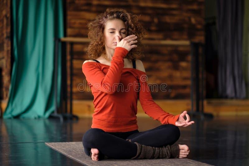 Młoda kędzierzawa kobieta robi joga ćwiczy, używać nadi shodhana pranayama zdjęcie stock