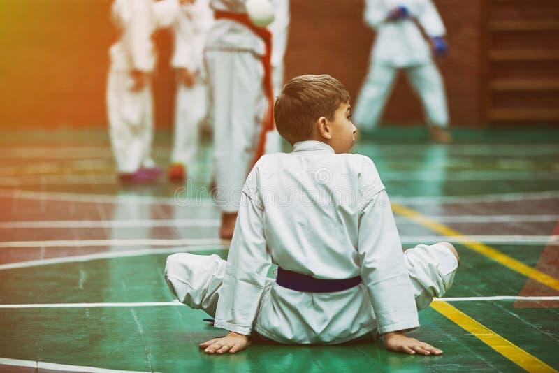 Młoda karate chłopiec rozgrzewkowa w górę kimona wewnątrz zdjęcia royalty free