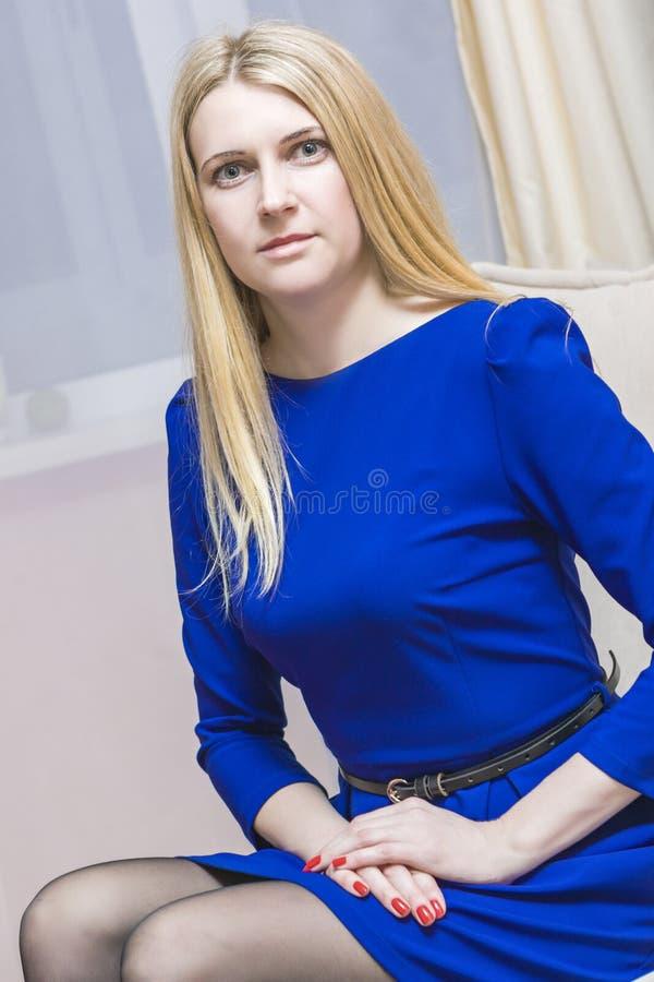 Młoda Kaukaska Blond kobieta w błękita Smokingowy Pozować na leżance Indoors obrazy stock