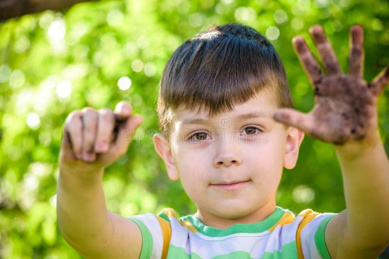 Młoda Kaukaska chłopiec pokazuje daleko jego brudne ręki po bawić się w brudzie i piasku obrazy royalty free