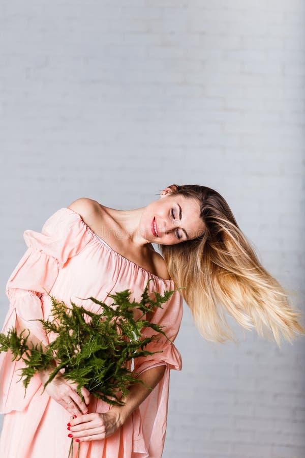 Młoda Kaukaska kobieta z luźnym blondynka włosy w luźnej brzoskwini sukni obrazy stock