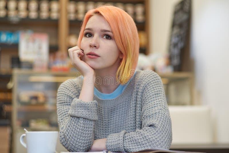 Młoda Kaukaska kobiety dziewczyna w przypadkowych ubrań puloweru obsiadaniu przy obraz stock