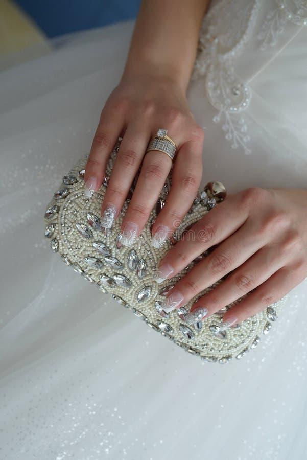 Młoda Kaukaska panna młoda z eleganckim manicure'em i rhinestone trzymający koralika upiększał sprzęgło zdjęcia stock