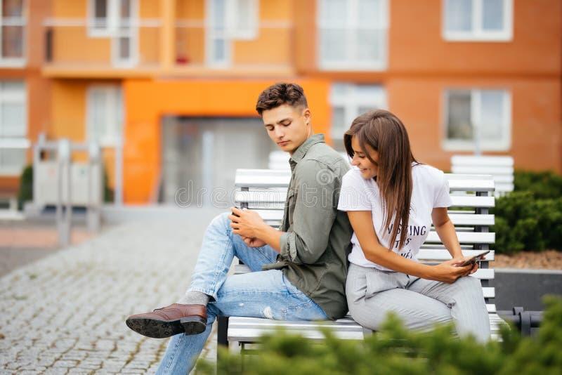 Młoda Kaukaska para na dacie, siedzi z powrotem popierać na parkowej ławki mienia telefonach komórkowych w rękach, używać app, ro fotografia stock