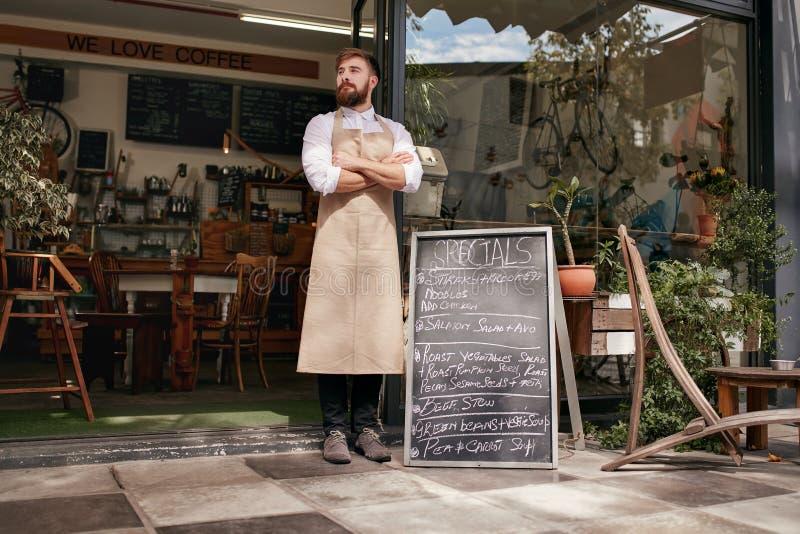 Młoda kelner pozycja w drzwi kawiarnia zdjęcia royalty free