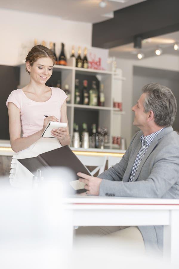 Młoda kelnerka bierze rozkaz od dojrzałego klienta przy restauracją fotografia stock
