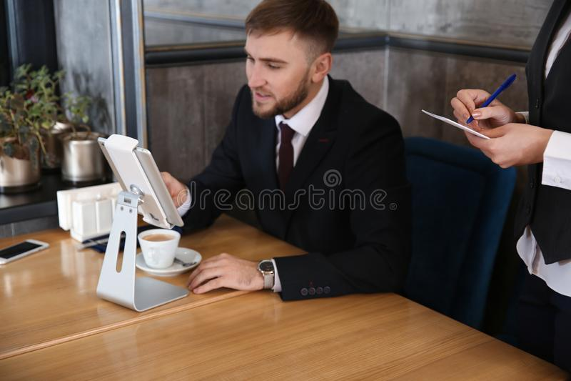 Młoda kelnerka bierze rozkaz od mężczyzny w restauracji zdjęcie royalty free